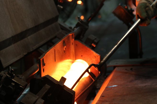 Pushing the stirred molten glass into the rollers.